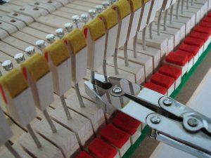 Réglage des attrapes d'un piano à queue avec la pince à couder