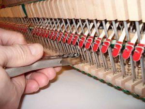 Réglage des attrapes avec la pince à couder sur un piano droit