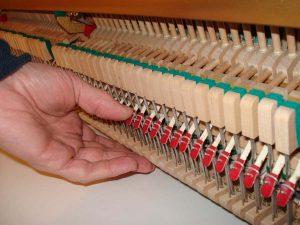 Réglage des lanières à la main sur un piano droitn piano droit