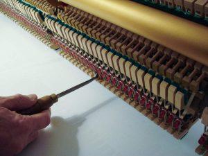 Réglage des lanières avec un outil sur un piano droit